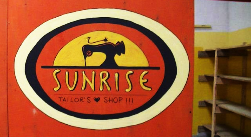 "Logo del ""Sunrise Tailor Shop"""